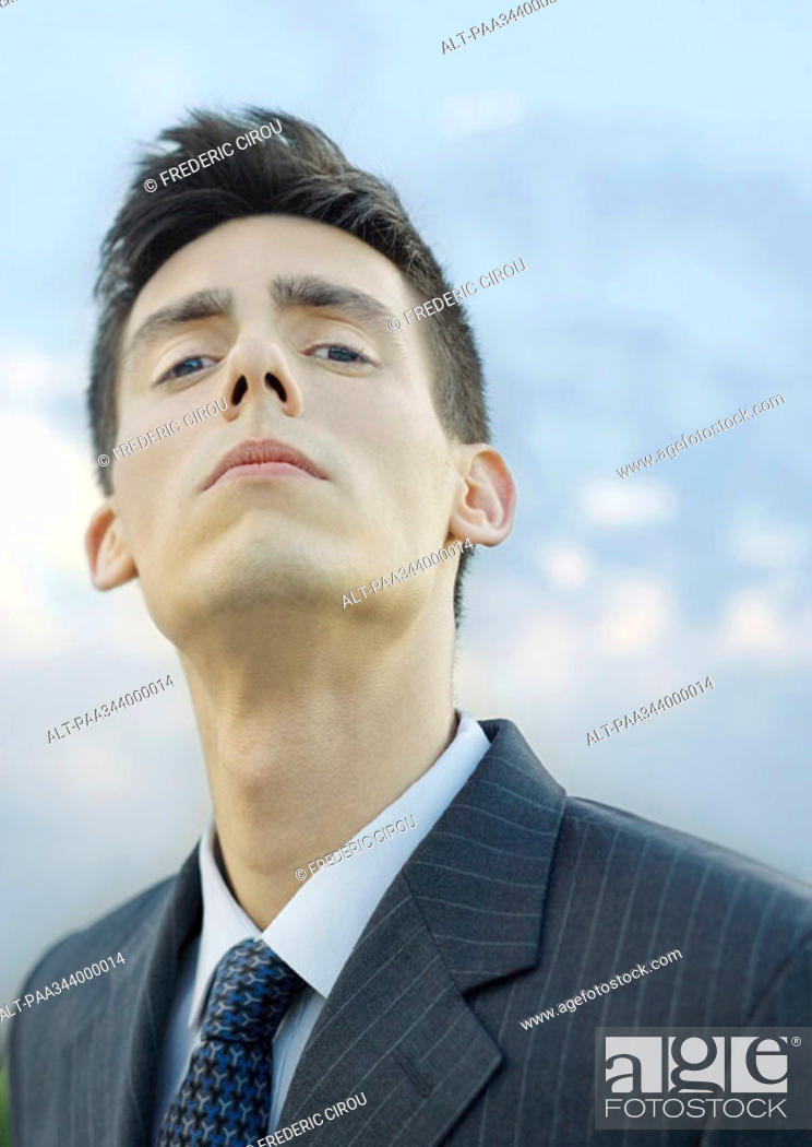 Stock Photo: Young businessman, looking down at camera, portrait.