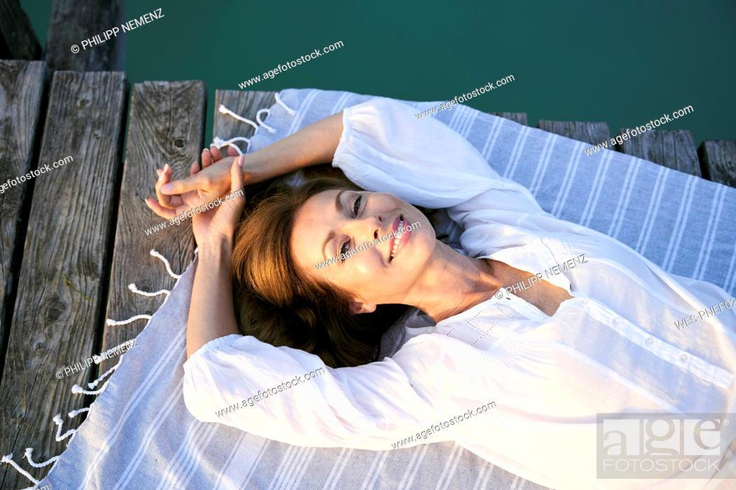 Photo de stock: Portait of smiling mature woman lying on a towel on a jetty at a lake.