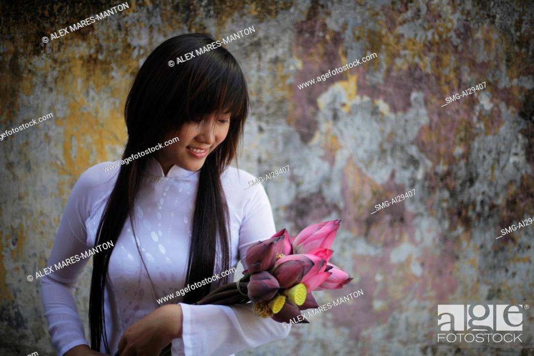 Stock Photo: Young woman wearing traditional Vietnamese outfit holding lotus flowers.