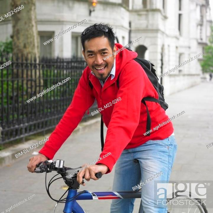 Stock Photo: Asian man on bicycle in urban area.