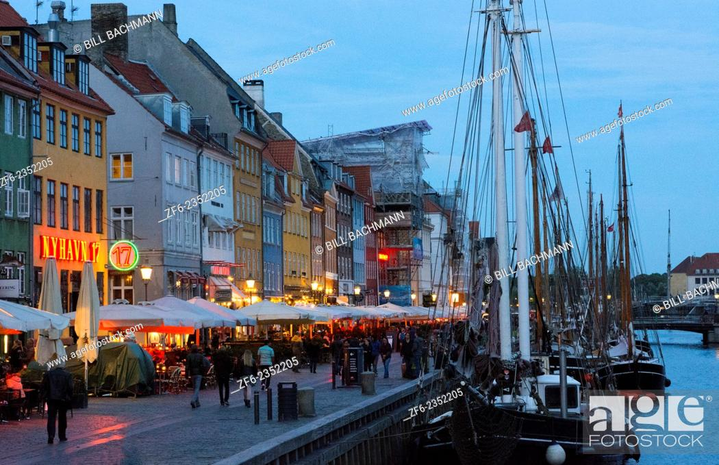 Stock Photo: Copenhagen Denmark famous Nyhavn night exposure of color homes and boats with crouds Kobenhavn tourists.