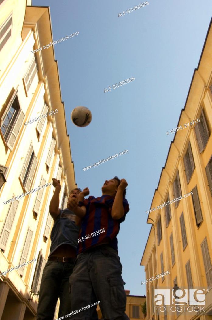 Stock Photo: Teenage boys heading soccer ball.