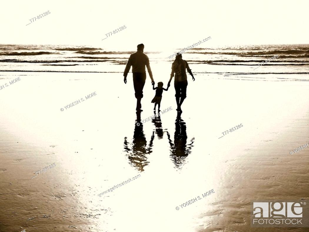 Stock Photo: A husband and wife, holding the hands of their baby girl, helping her walk with them through the ocean surf.