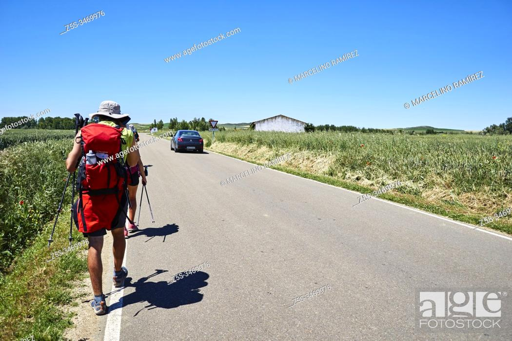 Stock Photo: Pilgrims with backpack walking on the left side of the road next to town of Itero de la Vega, Palencia, Castile and Leon, Spain, Europe.