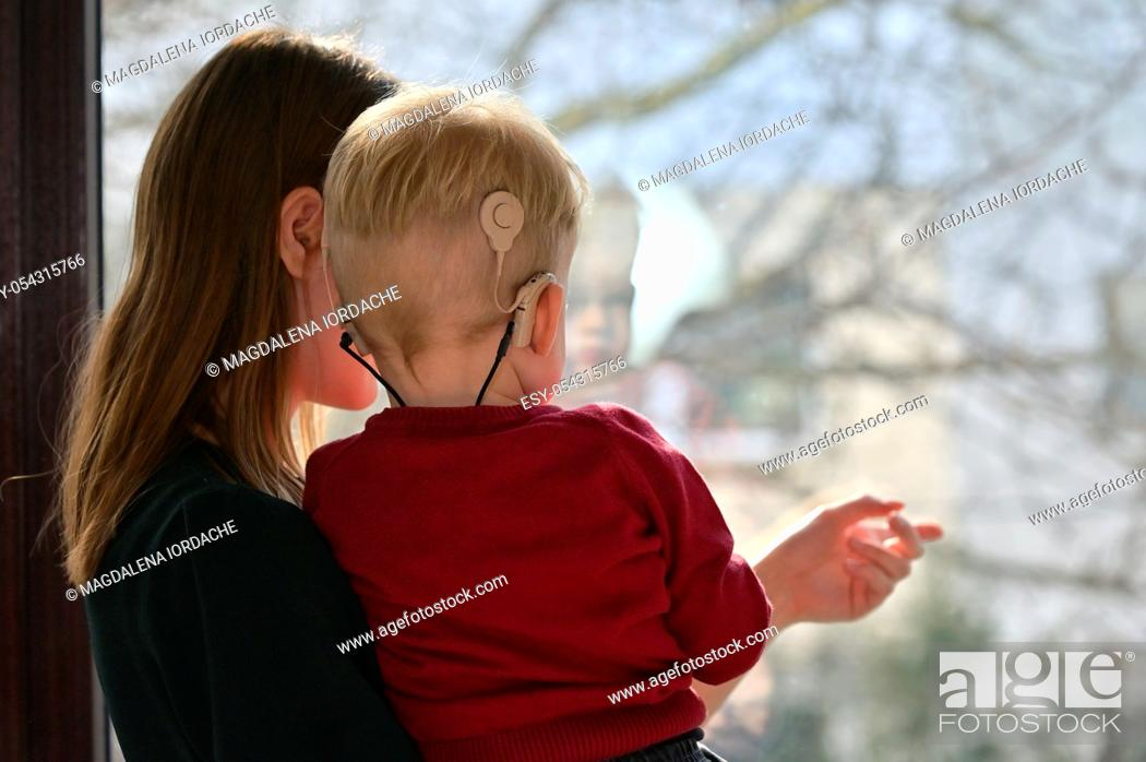 Stock Photo: A Boy With Cochlear Implants with his Mother.