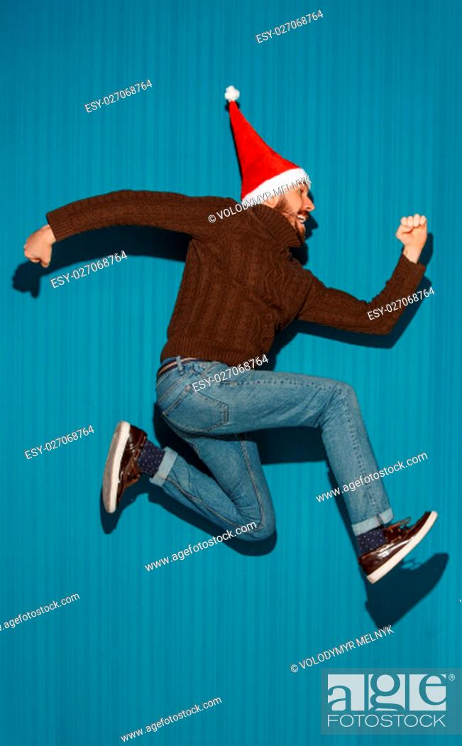 Stock Photo: The running christmas man wearing a santa hat on the blue studio background.