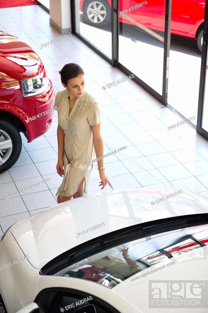 Stock Photo: Young woman looking at a car in a showroom.