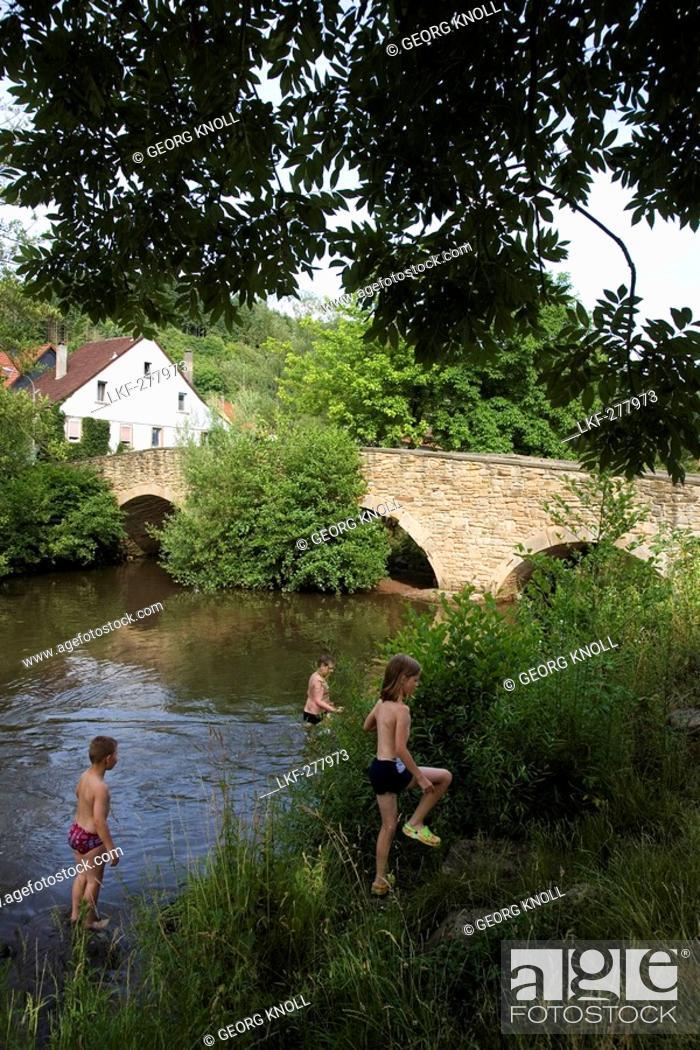 Stock Photo: Children bathing in river near old stone bridge, Lauterecken, Rhineland-Palatinate, Germany.