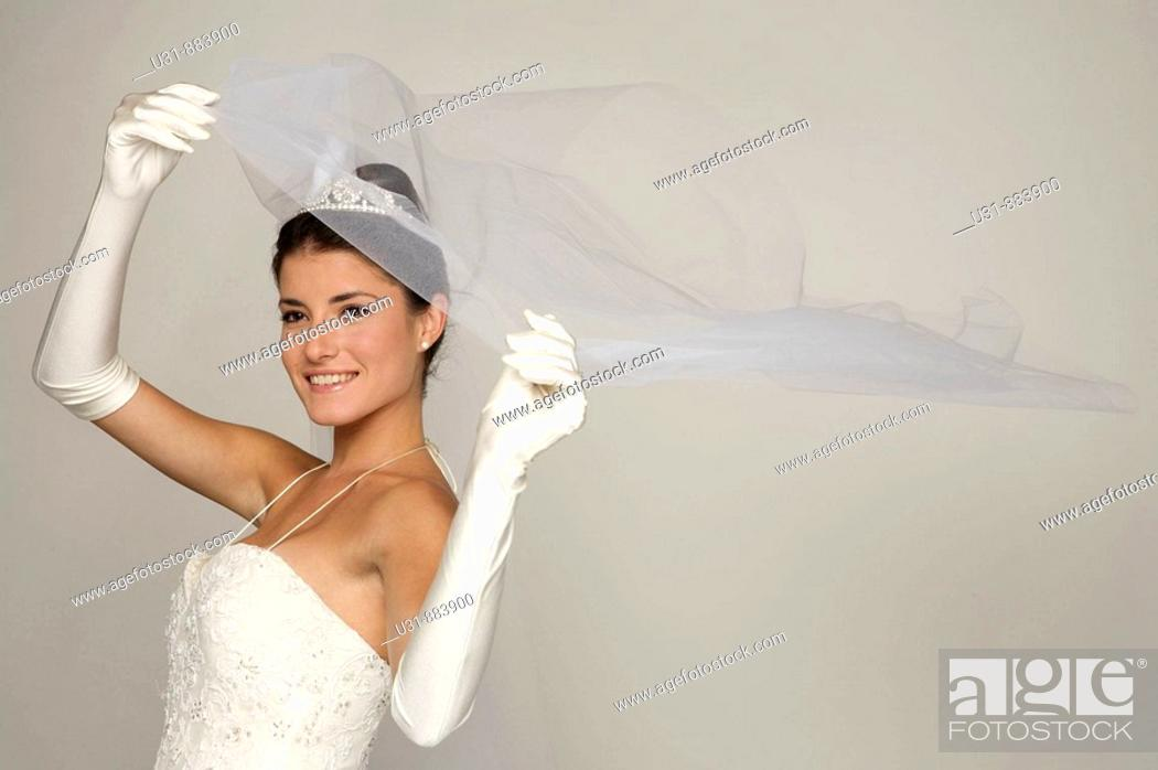 Stock Photo: Bride in her 20s discovers herself from under her veil.