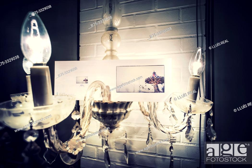 Stock Photo: Close up of a Chandelier lamp lit with a postcard with the image of a carousel. Mahon, Baleares, Spain, Europe.