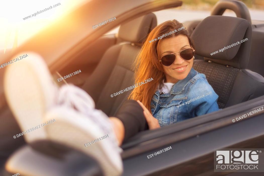 Stock Photo: woman enjoying convertible car at sunset.