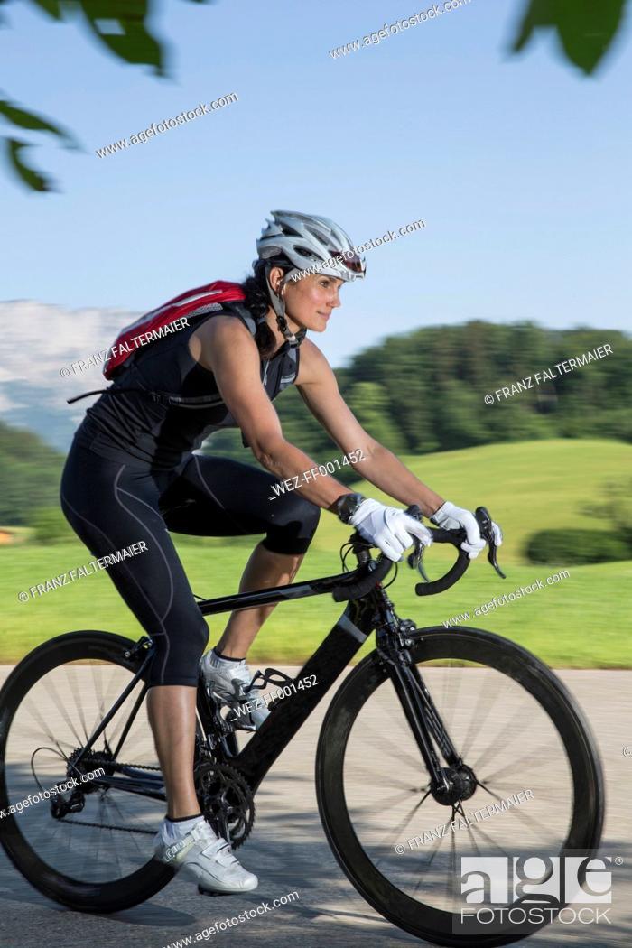 Imagen: Germany, Marktschellenberg, sportive woman riding bicycle.