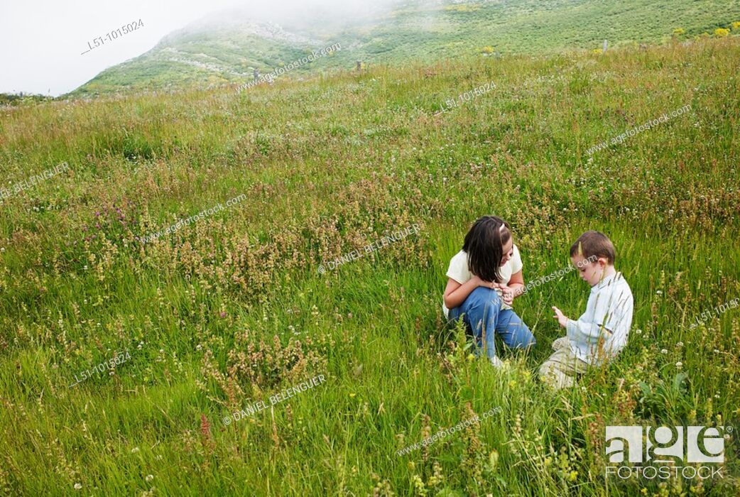 Stock Photo: Boy and girl playing on a meadow in the mountains of Somiedo.