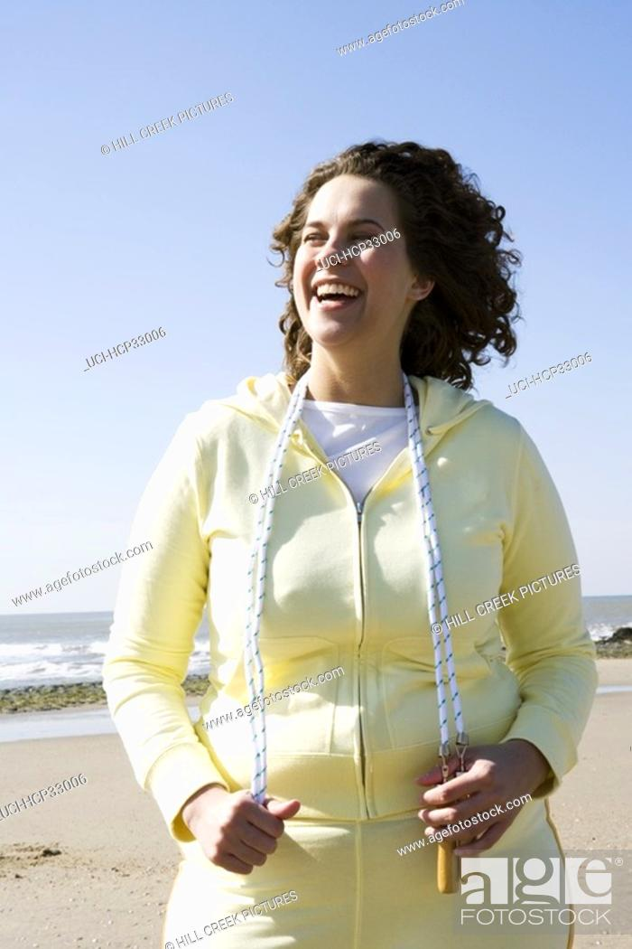Stock Photo: Woman holding jump rope at beach.