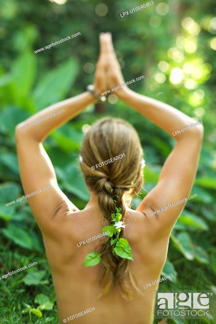 Stock Photo: Rear view of nude Caucasian mid-adult woman with hands overhead in yoga pose.