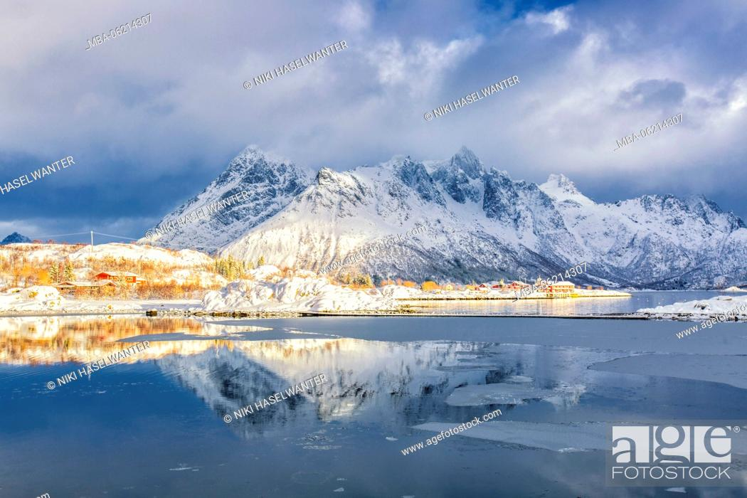 Imagen: Fjord in Norway at sunrise with ice and Reflection in foreground, village in the sunshine in the background, Lofoten.