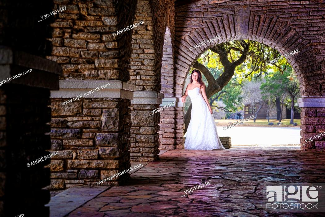 Stock Photo: Bridal portrait - A young bride in wedding dress posing at historical looking building at Garner State Park, Concan, Texas, USA, Female Caucasian, 23 years old.
