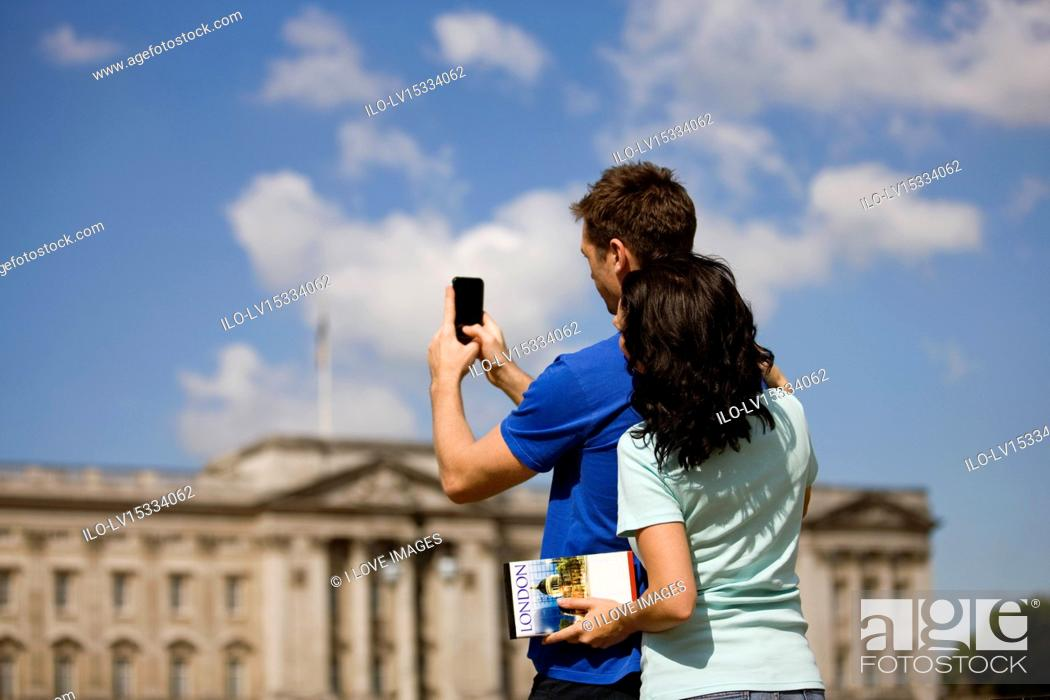 Stock Photo: A young couple taking a picture of Buckingham Palace.