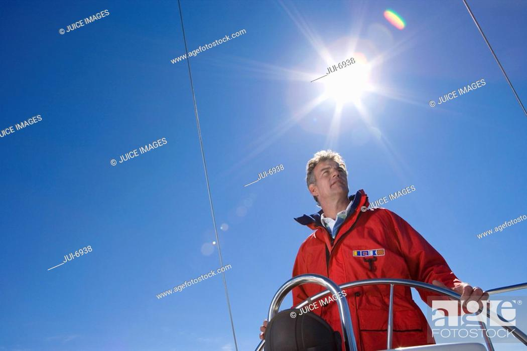 Stock Photo: Man in red jacket standing at helm of sailing boat out at sea, steering, low angle view lens flare.