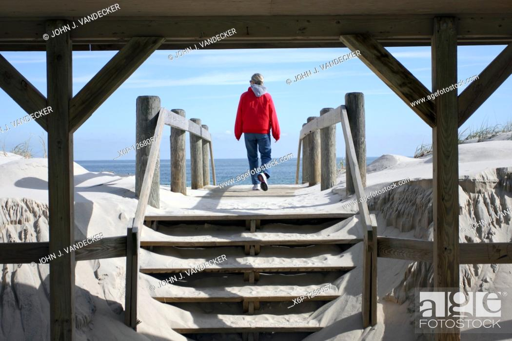 Stock Photo: Woman walking on to a beach through a boardwalk shelter  Lavalette, New Jersey, USA.