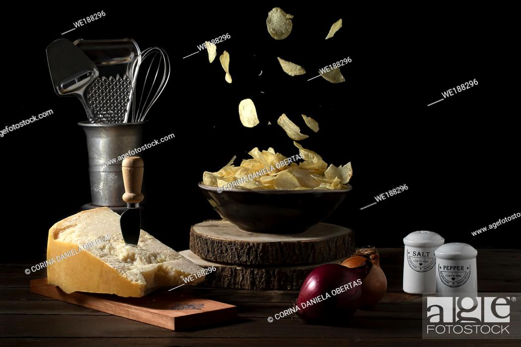 Stock Photo: Potato chips falling in a bowl on a table with parmesan cheese, onions, salt and pepper - Dark mood.