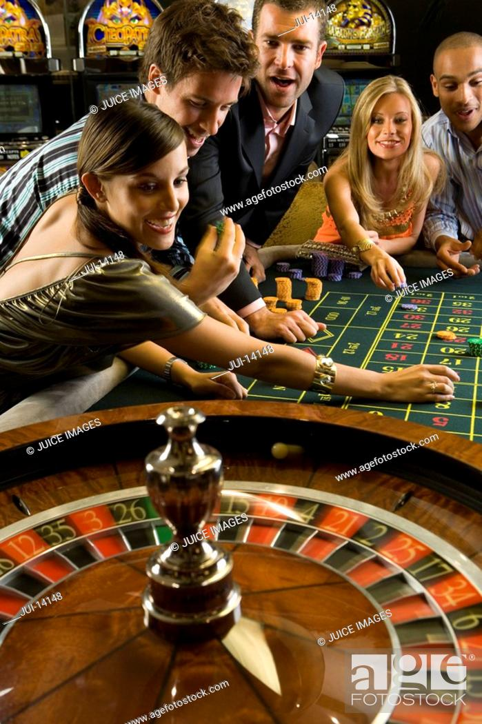 Stock Photo: Men and women gambling at roulette table in casino, elevated view.