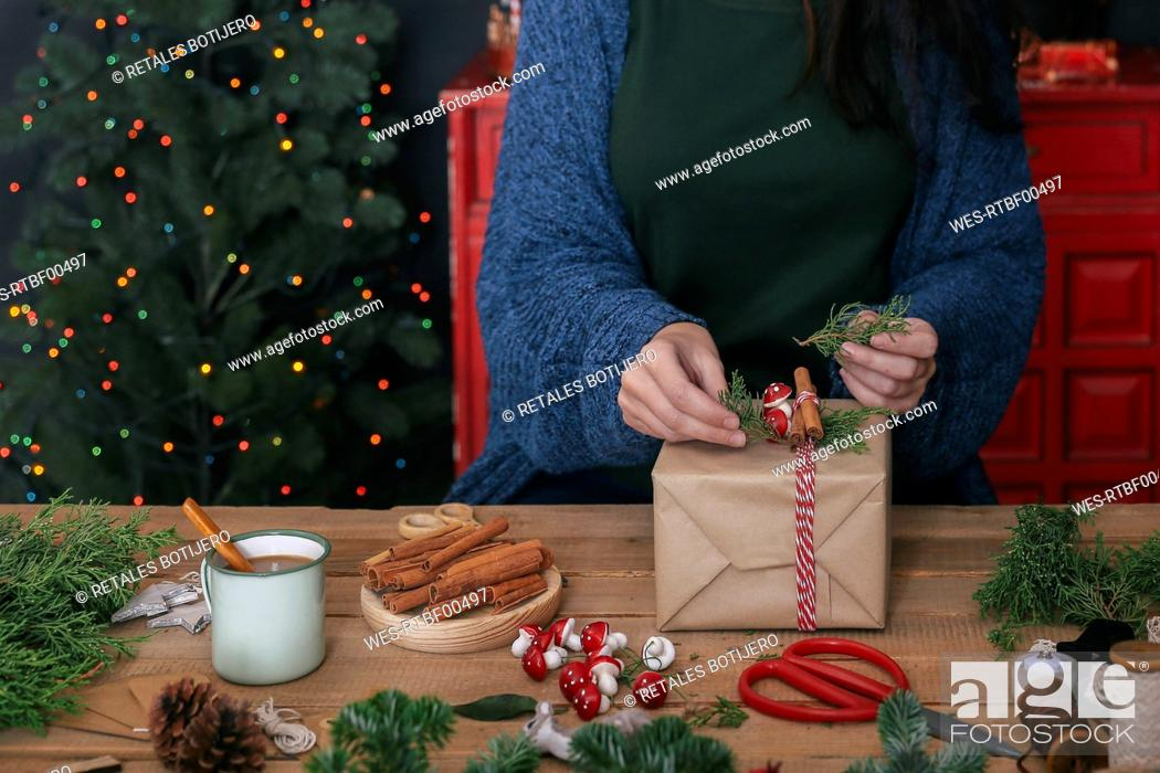 Stock Photo: Woman decorating Christmas present, partial view.