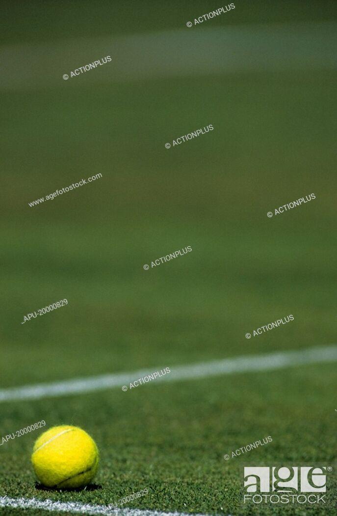 Imagen: Tennis ball on a grass court.