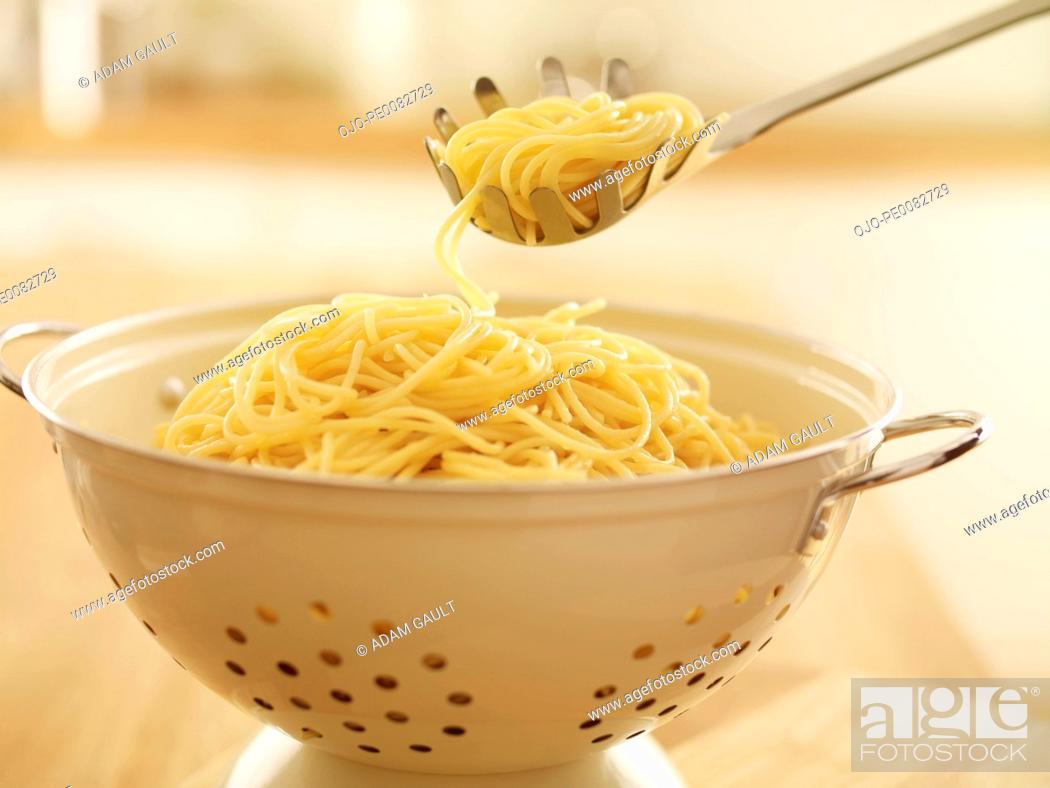 Stock Photo: Close up of spoon scooping spaghetti in colander.