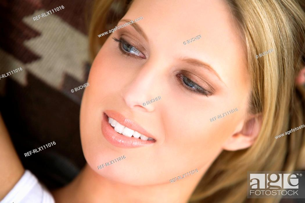 Stock Photo: Young woman relaxing on sofa.