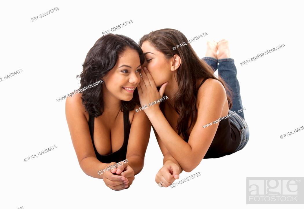 Stock Photo: Two beautiful young happy women laying, sharing telling a gossip secret, isolated.