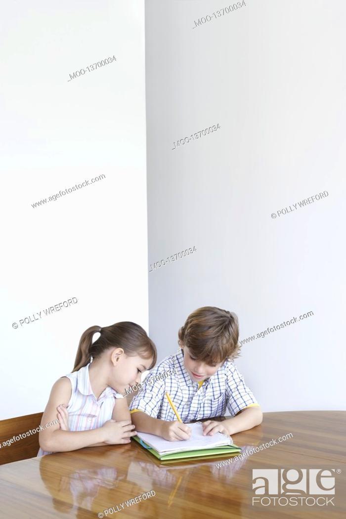 Stock Photo: Boy 7-9 and girl 5-6 doing homework together.