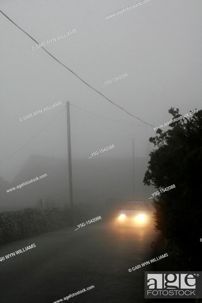 Stock Photo: car in thick fog on country lane.