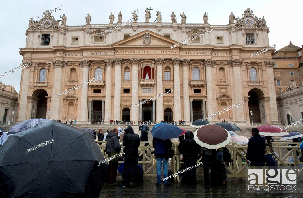 Stock Photo: Journalists await the smoke signal from the chimney of the Sistine Chapel in the rain on St. Peter's Square in Vatican City, Vatican, 12 March 2013.