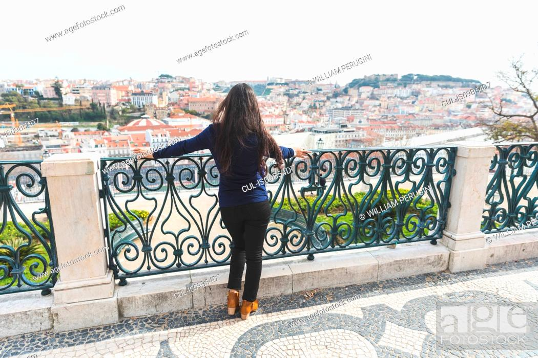 Stock Photo: Rear view of woman looking away at elevated view of Lisbon, Portugal.