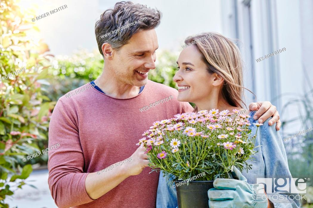 Stock Photo: Smiling couple with flowers in front of their home.