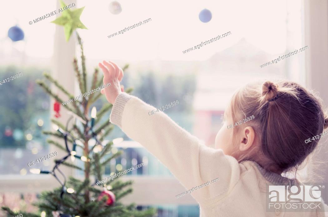 Stock Photo: Girl reaching for start on Christmas tree.