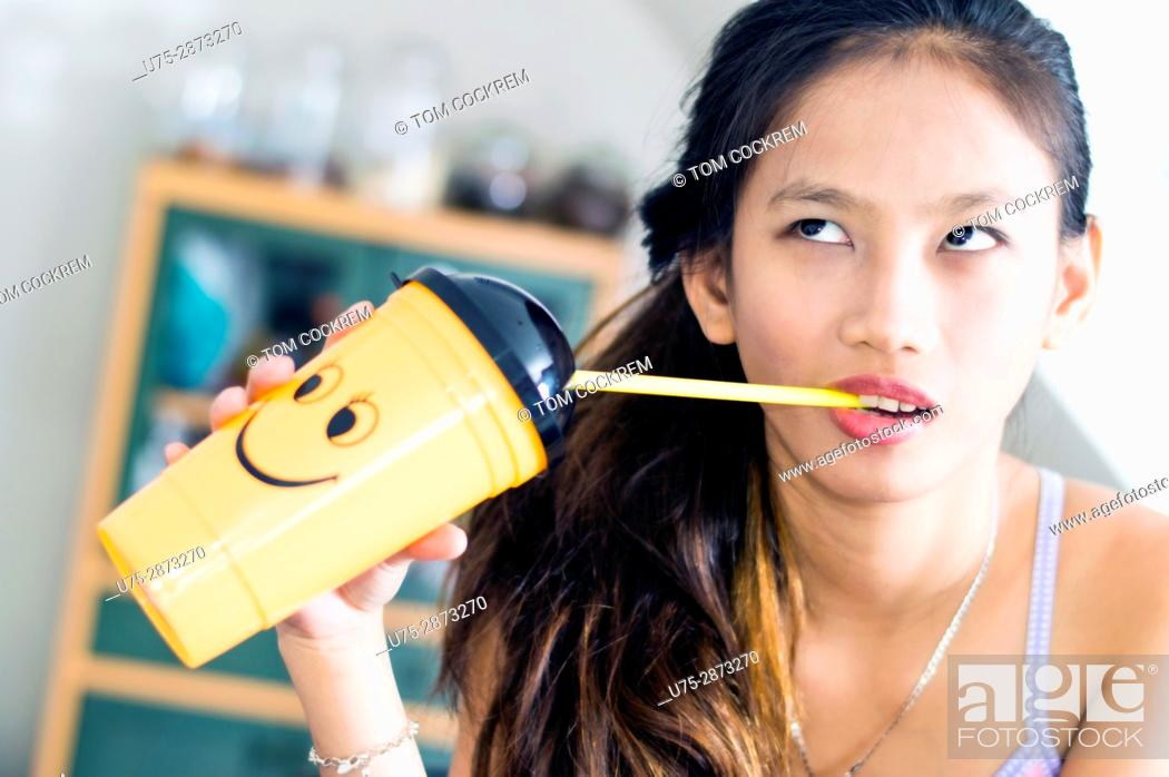 Stock Photo: Young attractive Asian woman with novelty smiley plastic cup in an indoors setting.