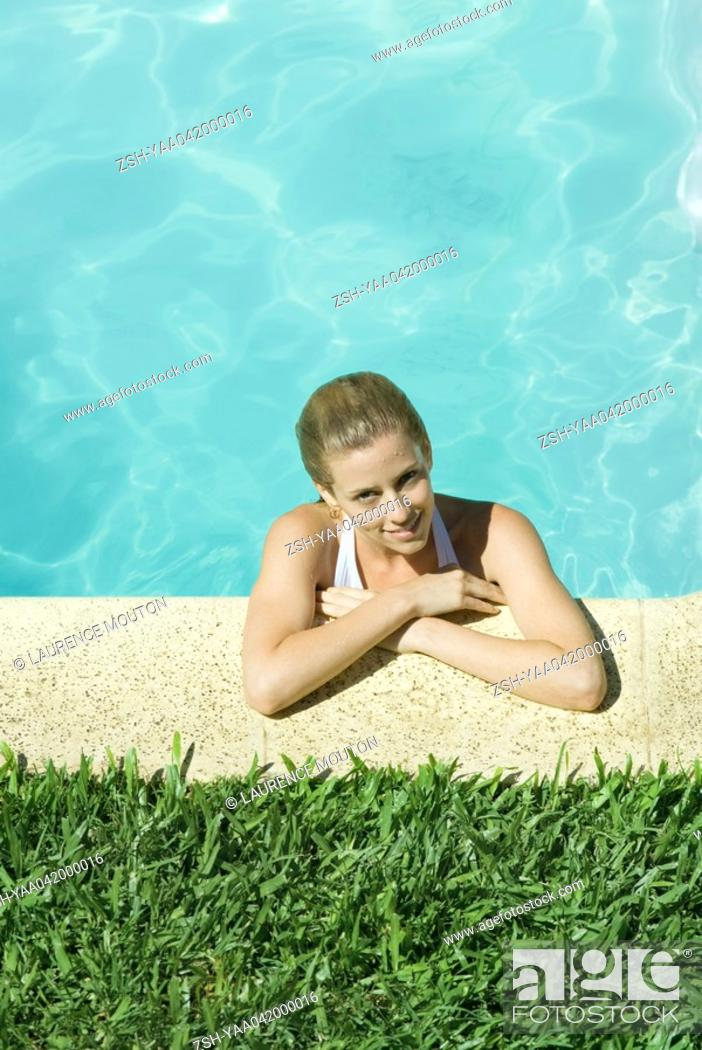Stock Photo: Young woman resting arms on edge of pool.