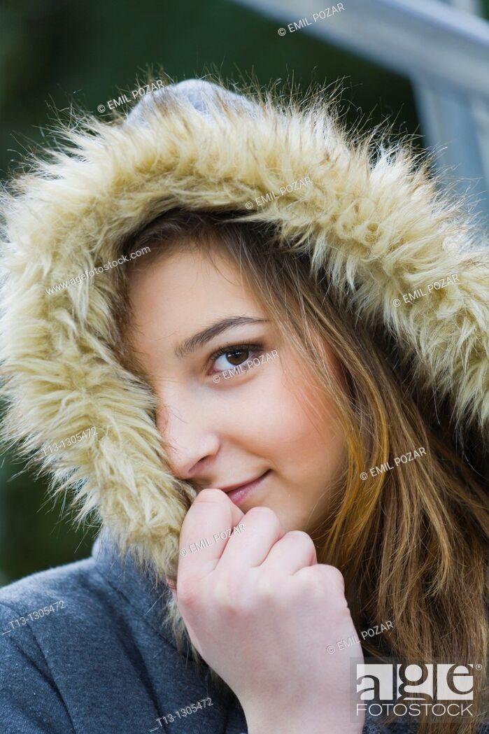 Stock Photo: Shy teen girl is peeking with one eye under the hood.
