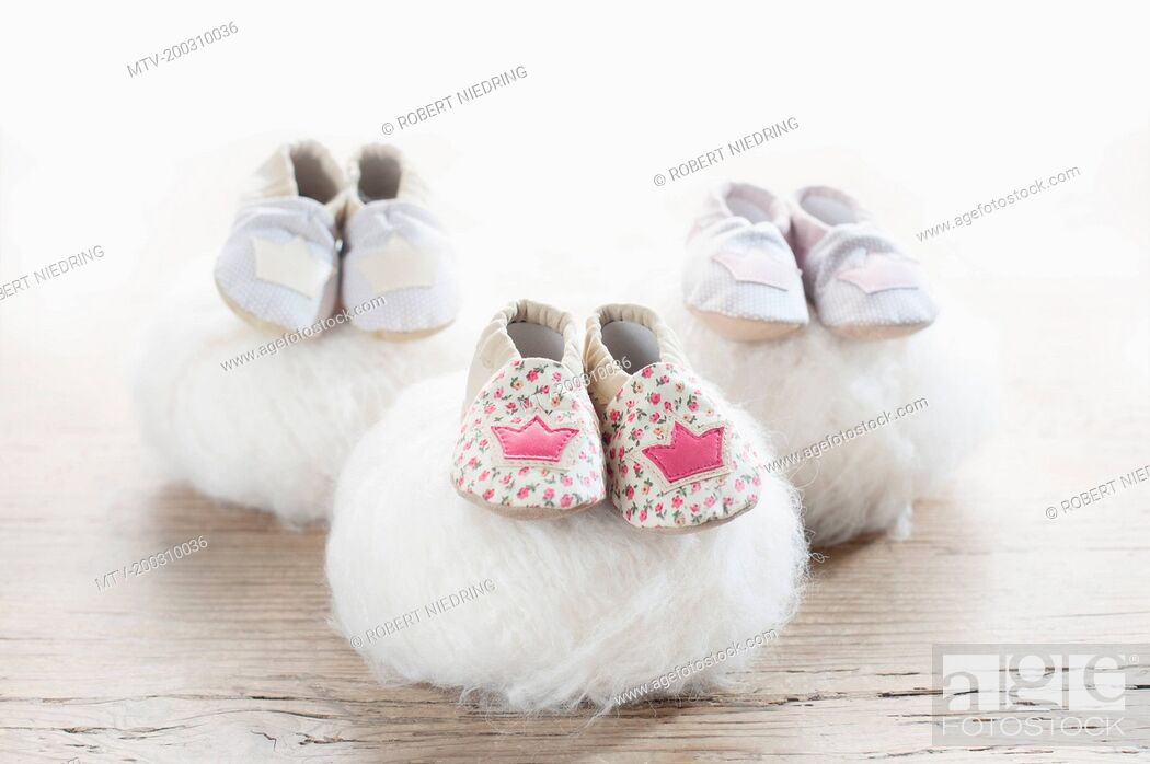 Stock Photo: Three pairs of baby shoes on woolen soft balls, Bavaria, Germany.