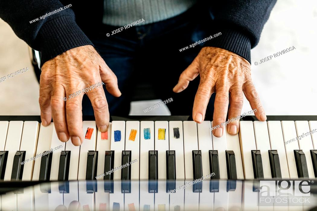 Imagen: Hands of senior man playing piano, close-up.