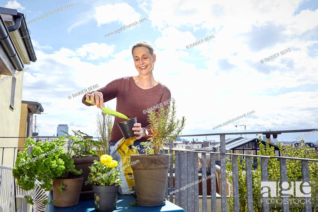 Stock Photo: Smiling mature woman caring for plants on balcony.