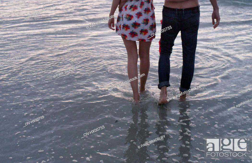 Stock Photo: Young couple walking in ocean surf.