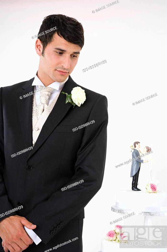 Stock Photo: Worried looking groom with wedding cake.