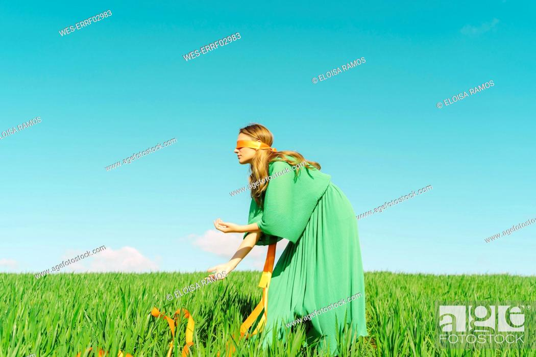 Stock Photo: Blindfolded young woman wearing a green dress standing in a field.