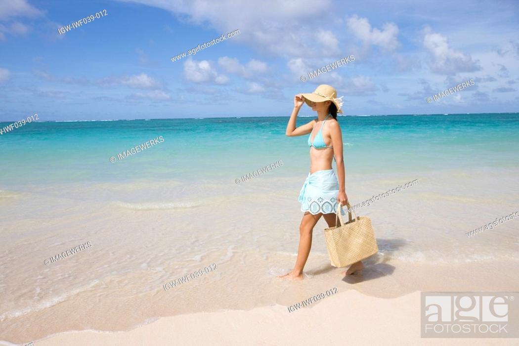 Stock Photo: A woman walking on beach.