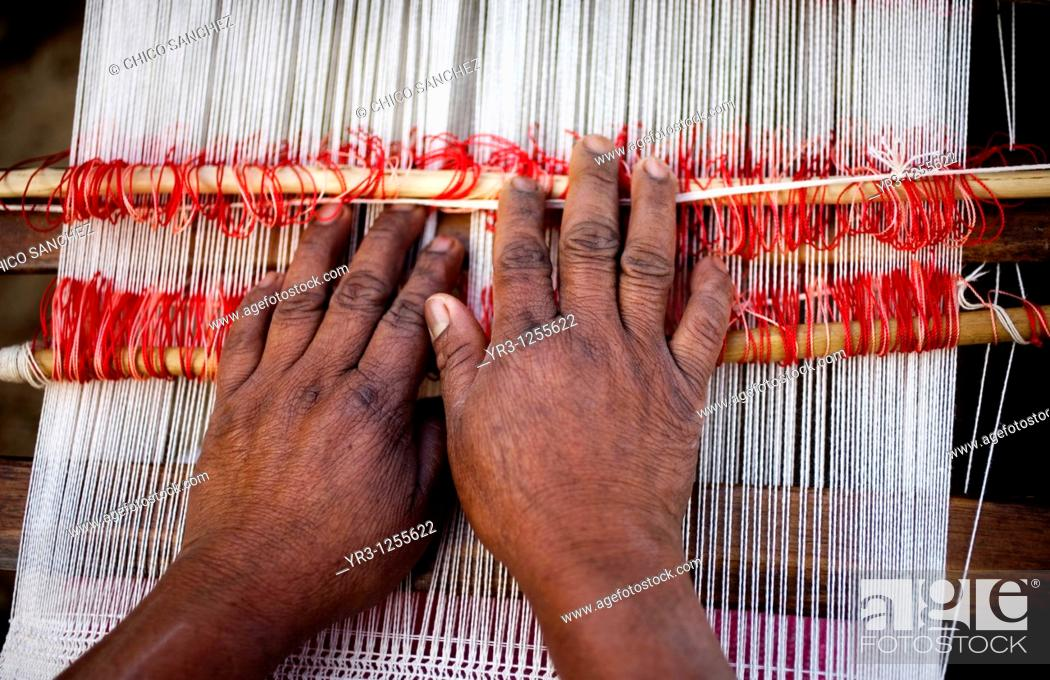 Stock Photo: A woman weaves a shawl outside her home in San Andrés Tzicuilan, on the outskirts of Cuetzalan del Progreso, Mexico. Cuetzalan is a small picturesque market.