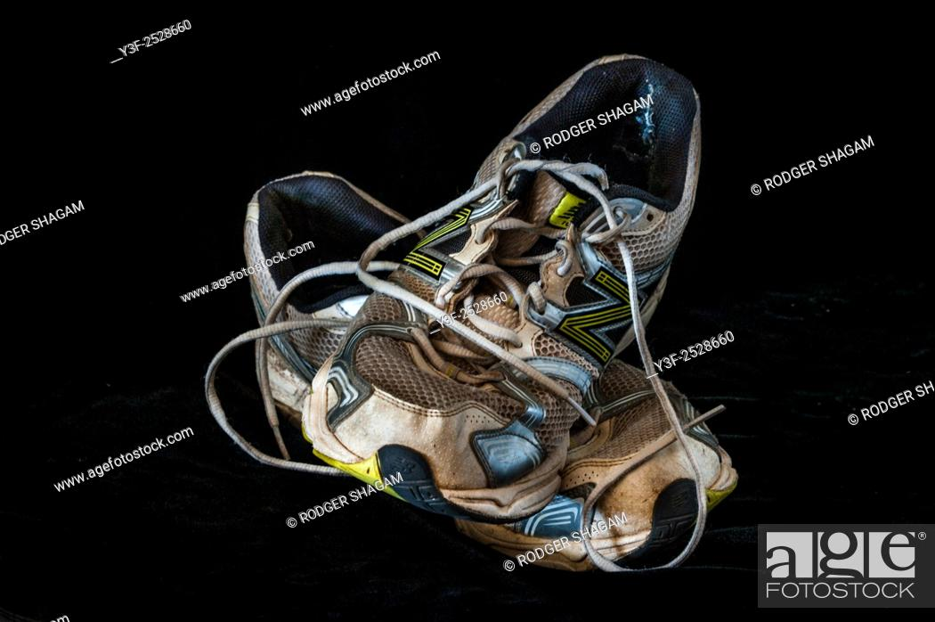 Stock Photo: An old pair of running shoes, worn out and ready to be trashed.