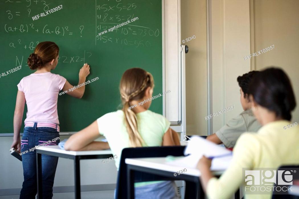 Stock Photo: Group of school children 10-13 in classroom looking at blackboard.